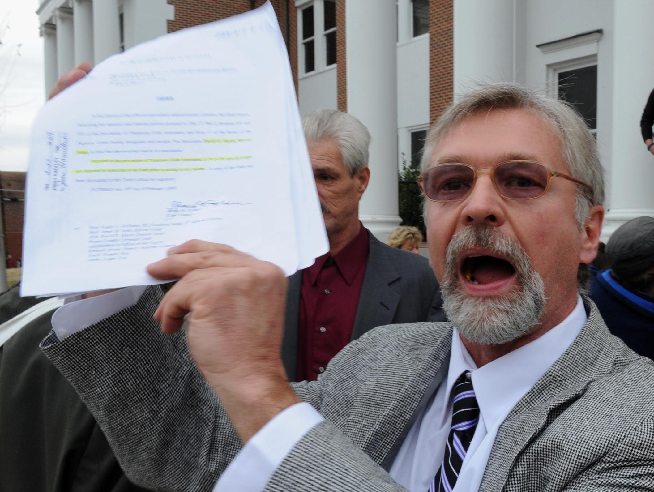 Rocky Houston holds a court order while protesting the sale of a portion of his family farm on the front steps of the Roane County Courthouse Tuesday, Jan. 4, 2011. Leon Houston's former attorney James Logan auctioned the land for unpaid legal fees.  After no buyers came forward Logan purchased the land for $150,000.