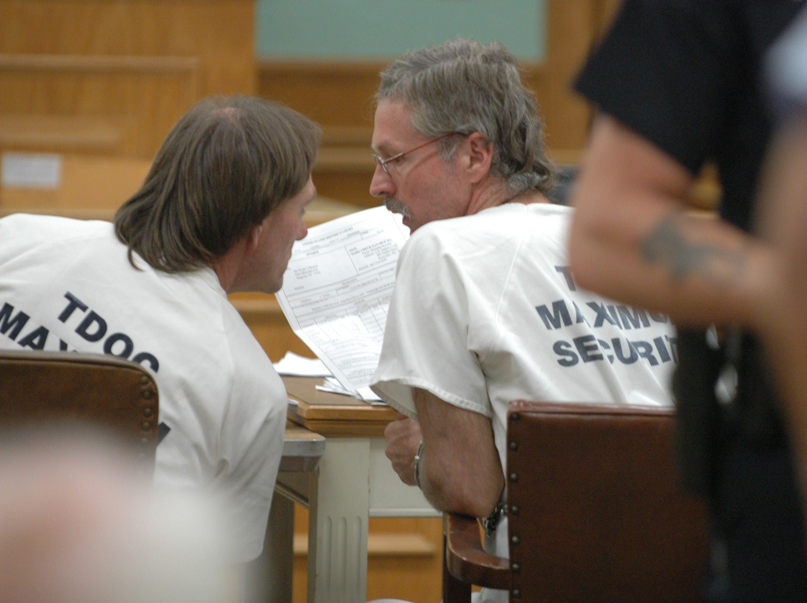 Clifford Leon Houston, left, and Rocky Joe Houston, right, speak during a hearing at the Roane County Courthouse where they stand accused of the fatal ambush of a sheriff's deputy and his ride-along friend in May.  The courthouse was locked down and security was significant during the hearing.