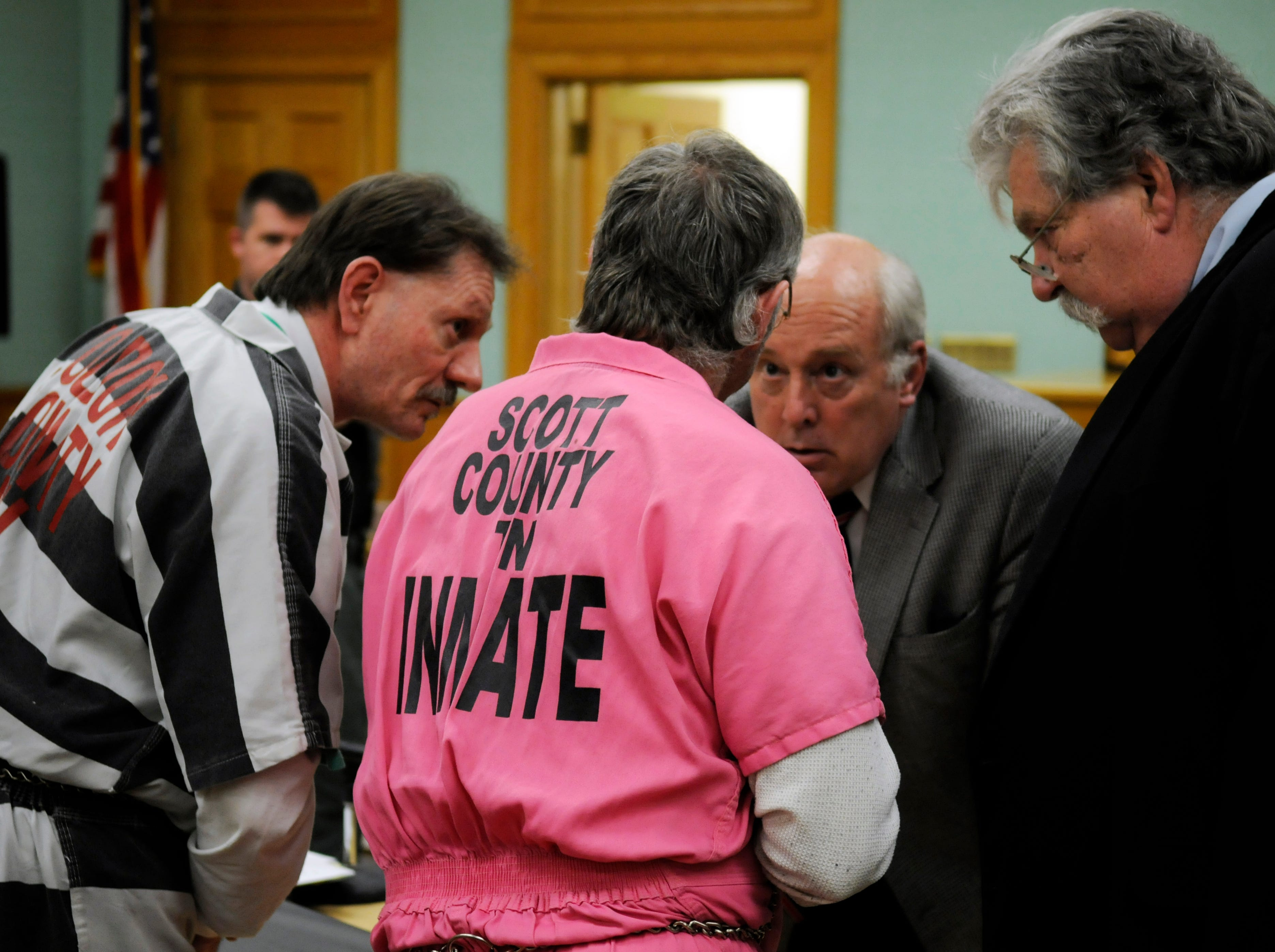 Leon, left, and Rocky, center, Houston talk to their attorneys Jim Logan, third from left, and Randy Rogers, right following a hearing Monday to set the conditions if they are able to make bond in Roane County. The Houstons are accused of murder in the May 11, 2006 shooting deaths of Roane County Sheriff's Department Deputy William Birl Jones and his ride-along pal Gerald Michael Brown when the pair showed up at Leon Houston's home in the Ten Mile community.