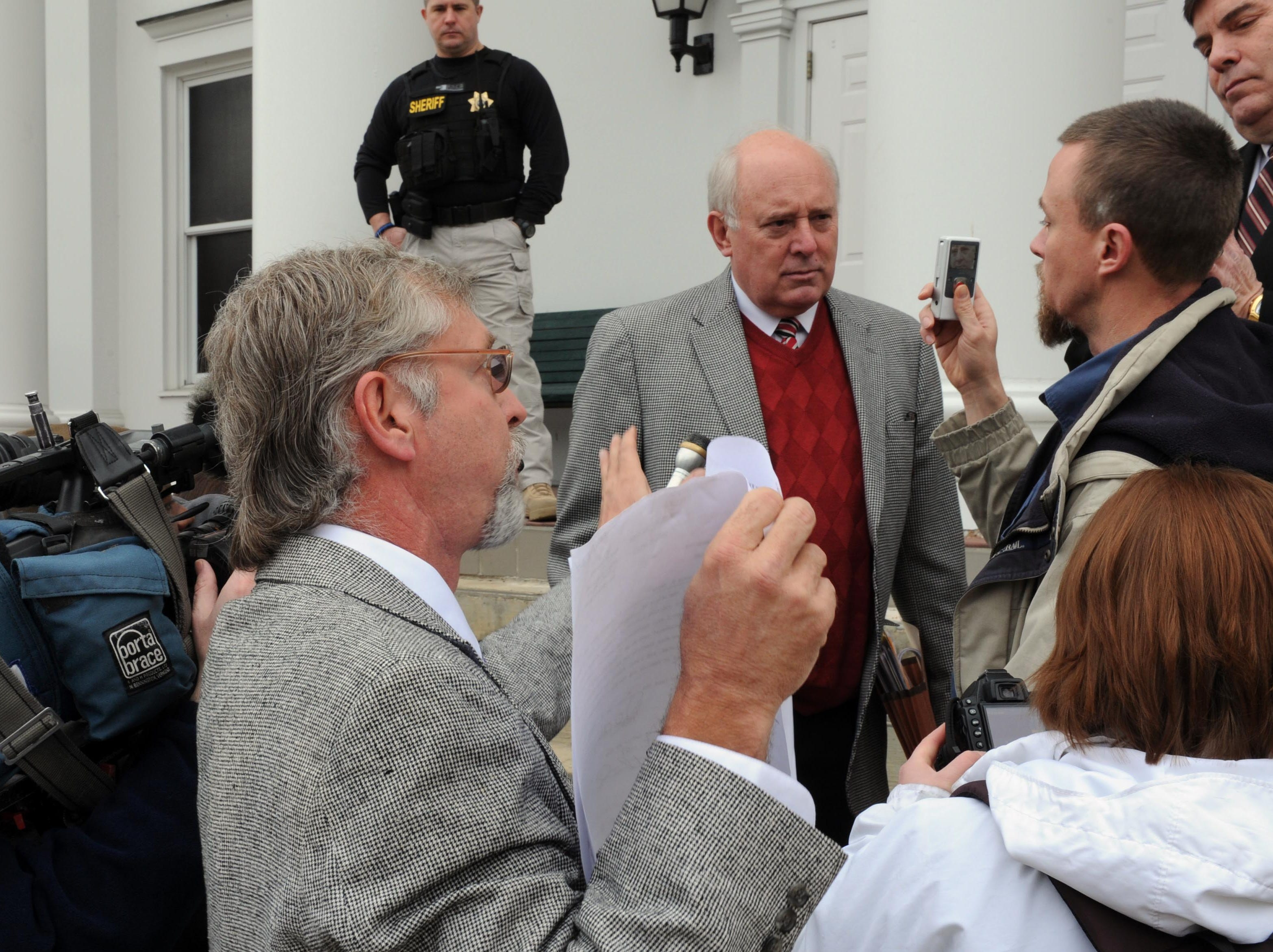 Rocky Houston, center, tries to ask Leon's former attorney James Logan what the property sold for on the front steps of the Roane County Courthouse Tuesday, Jan. 4, 2011. Leon's former attorney James Logan auctioned the land for unpaid legal fees.  After no buyers came forward Logan purchased the land for $150,000.