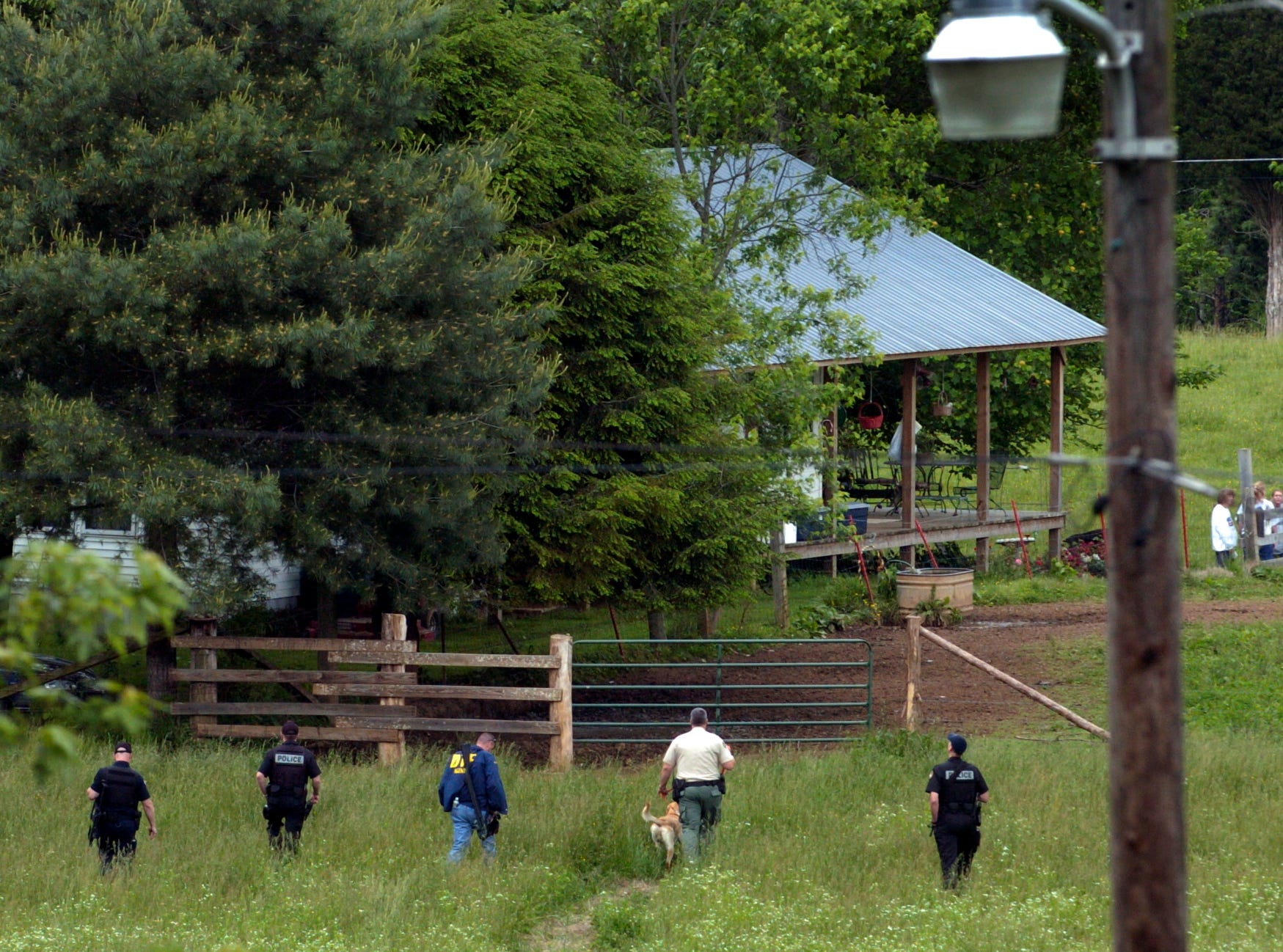 A line of police officers and a search dog walk across the field seperating Clyde Houston's house (top of frame) and the suspects uncle, Ray Johnson where they fled after the shooting. Leon Houston and his brother, Rocky, allegedly ambushed and killed Deputy Bill Jones, 53, and friend Mike Brown Thursday evening.
