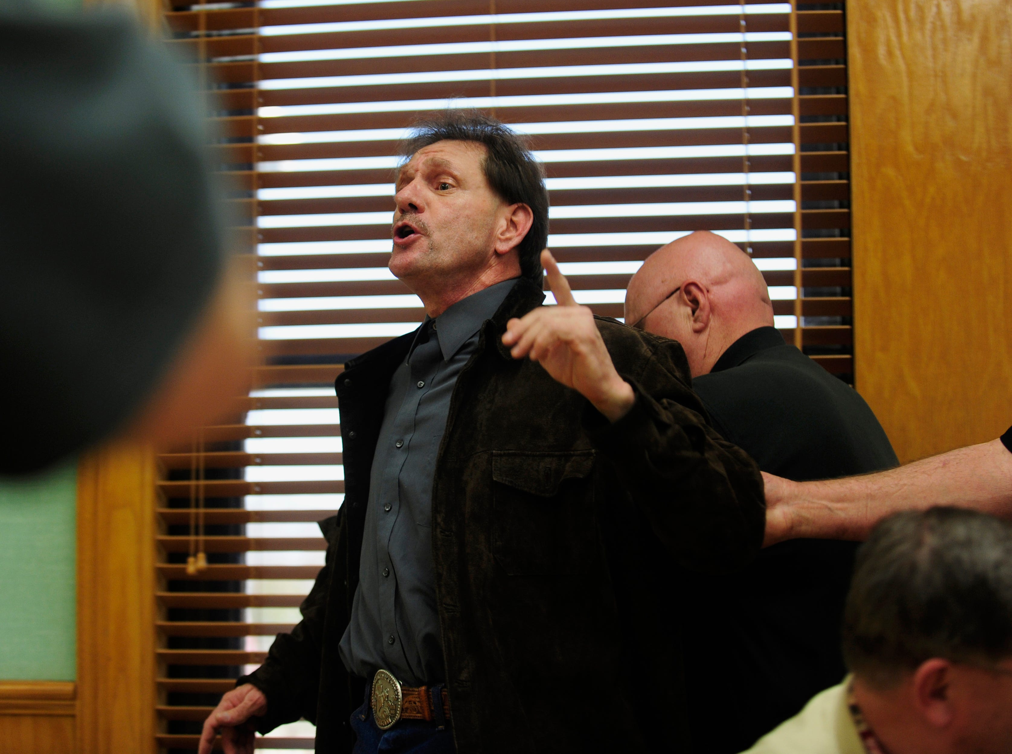 Leon Houston, center, continues to yell as he is taken into custody Friday, Mar. 19, 2010 by Roane County Sheriff Major Ken Mynatt on contempt of court after an outburst directed at Judge Kerry Blackwood. The outburst came during a motions hearing for Leon's brother Rocky Joe Houston.