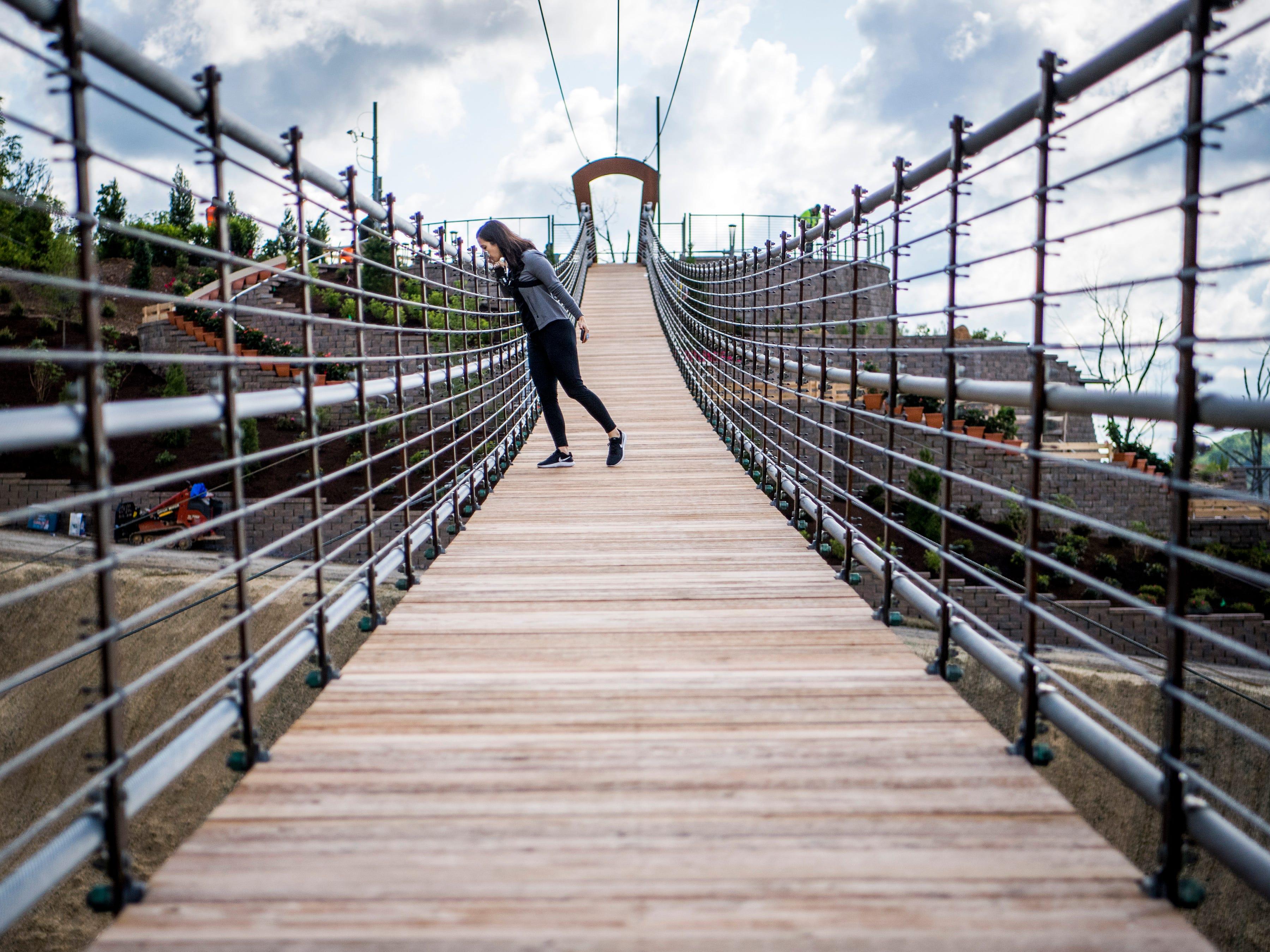 Knoxville News Sentinel reporter Brenna Mcdermott peers over the side of the Gatlinburg SkyBridge, North America's longest pedestrian suspension bridge, on Tuesday, May 14, 2019.