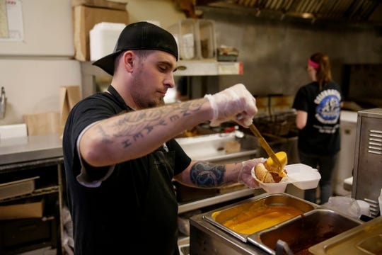 Matthew Sparger prepares a chili cheese dog at AJ's, Tuesday, May 14, 2019, in West Lafayette.  The new location will be located at 302 Vine Street.