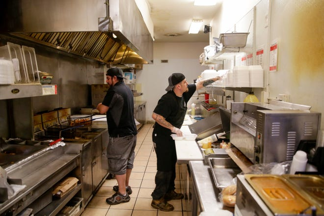Jose Foleman, left, and Matthew Sparger prepare orders in the kitchen at AJ's, Tuesday, May 14, 2019, in West Lafayette.  The new location will be located at 302 Vine Street.