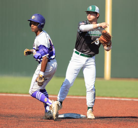 Opelousas Catholic's Cameron Gauthier looks to first as Ouachita Christian's Connor Mulhern turns a game ending double play during the LHSAA Baseball State Tournament Division IV Championship at McMurray Park in Sulphur, Louisiana on Monday, May 13, 2019.