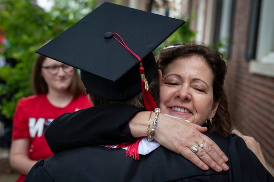 Louisville native Clay Harville, left, gets a hug from his mother, Mary Harville, before the start of the Topper Walk at Western Kentucky University. Harville is the first to graduate from WKUÕs autism program with a degree in special education teaching. May 11, 2019
