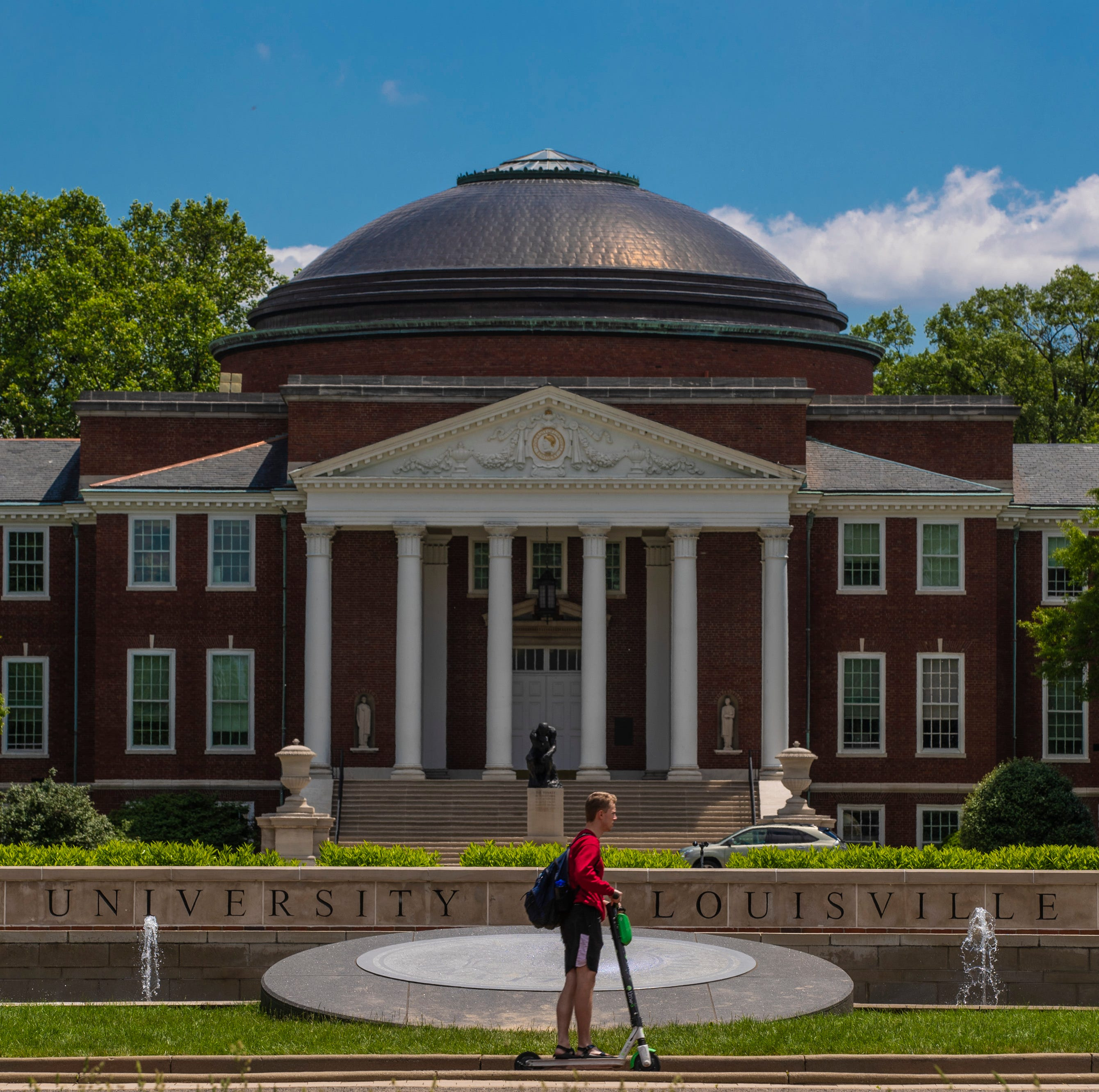 A student rides a Bird scooter past Grawemeyer Hall Tuesday on the University of Louisville campus. May 14, 2019