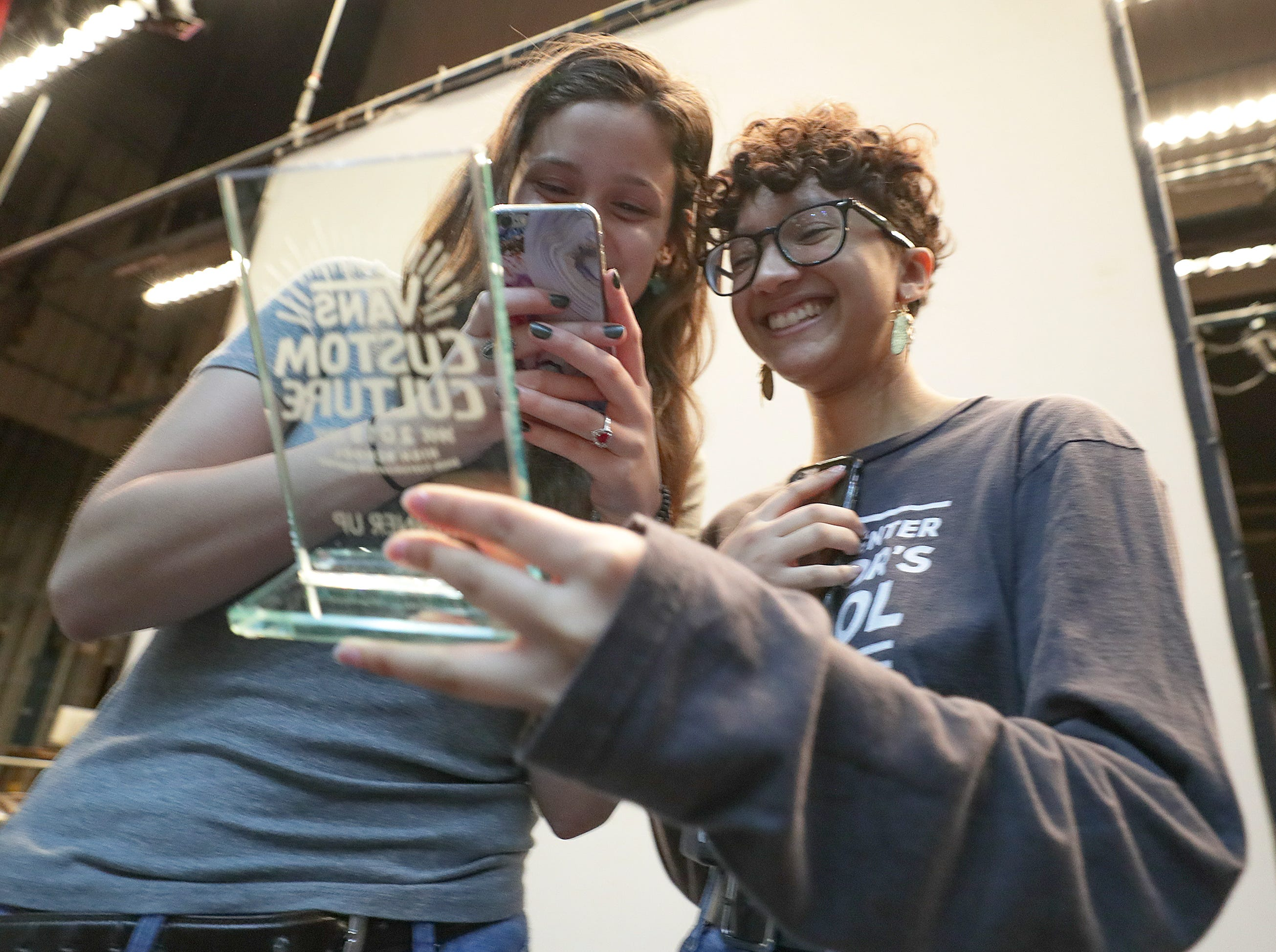 Atherton students Olivia Bunger and Natasha Campbell take photos of a trophy from Vans as part of the Custom Culture contest.  The contest had students use the distinctive footwear to design shoes that depict their state.  Atherton was one of the runner ups and received $10,000 from Vans.May 14, 2019
