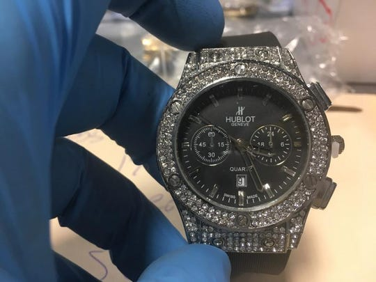 A U.S. Customs and Border Protection officer holds a fake Hublot watch that was recently seized.