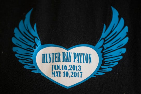 Family members wear custom shirts with the birth date and date of death of Hunter Payton, who died from head injuries while in the foster care of Billy and husband Travis Embry-Martin in 2017. May 13, 2019