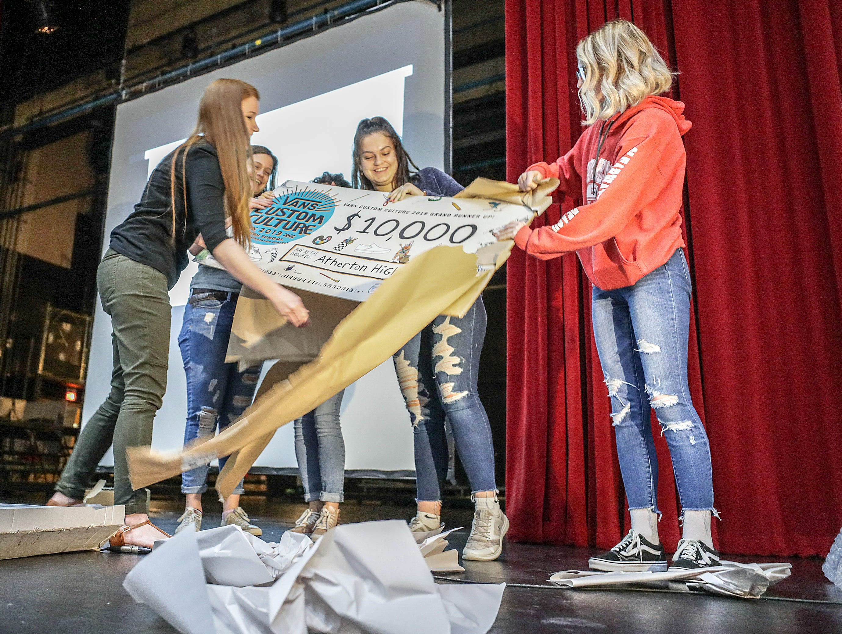 Atherton students unwrap a check from Vans as part of the Custom Culture contest.  The contest had students use the distinctive footwear to design shoes that depict their state.  Atherton was one of the runner ups and received $10,000 from Vans.May 14, 2019