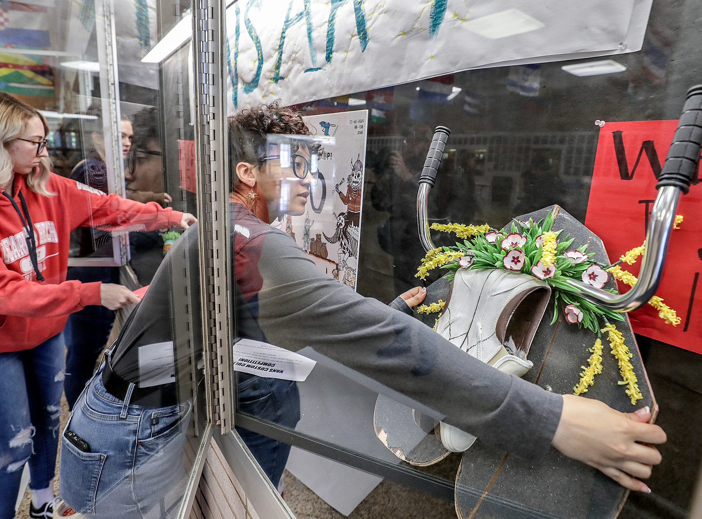 Atherton senior Natasha Campbell places a piece of art into a glass case after an assembly as part of the Vans Custom Culture contest.  The contest had students use the distinctive footwear to design shoes that depict their state.  Atherton was one of the runner ups and received $10,000 from Vans.May 14, 2019