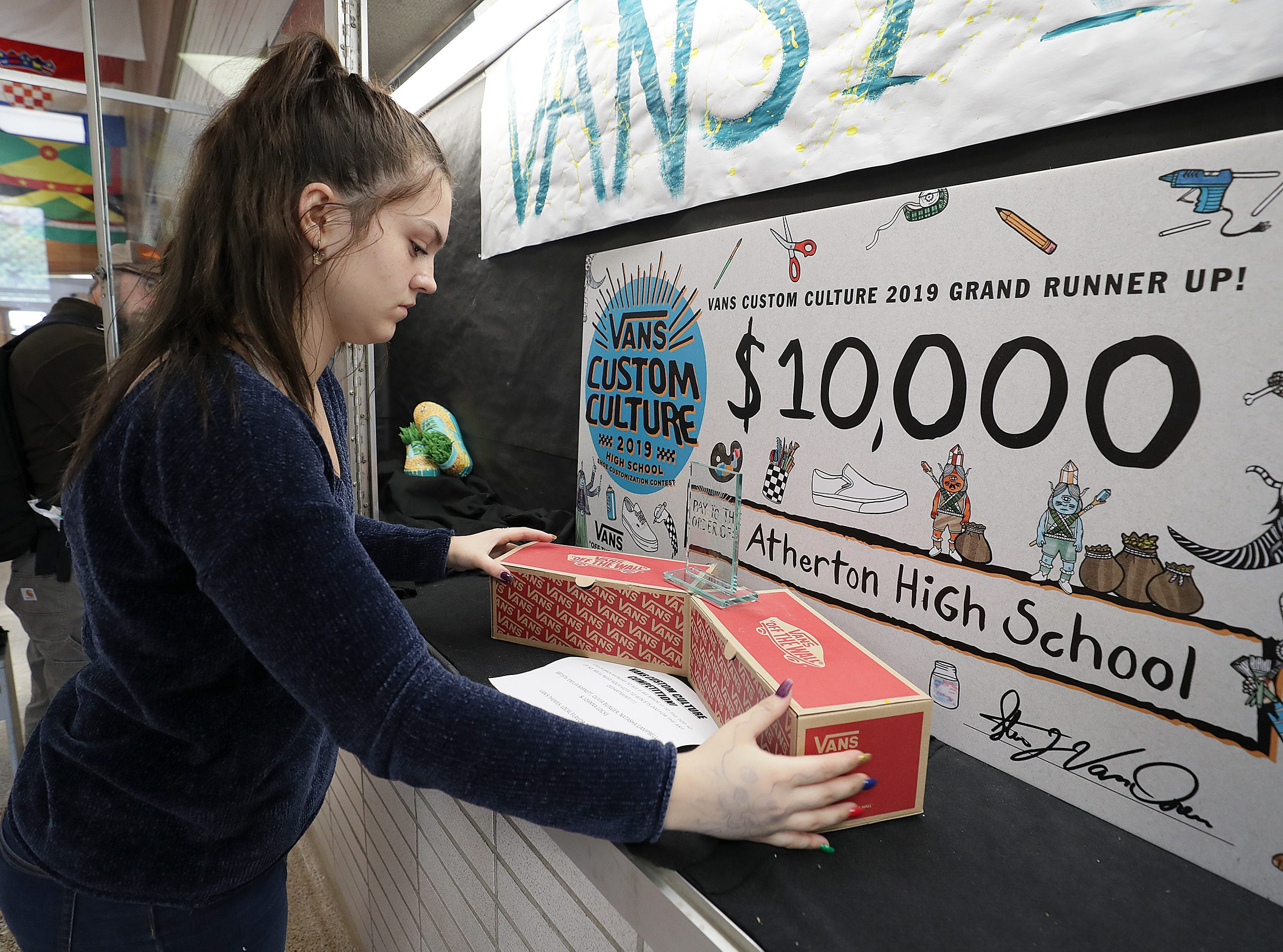Atherton junior Joanna Locke tweaks a display with a trophy after an assembly as part of the Vans Custom Culture contest.  The contest had students use the distinctive footwear to design shoes that depict their state.  Atherton was one of the runner ups and received $10,000 from Vans.May 14, 2019