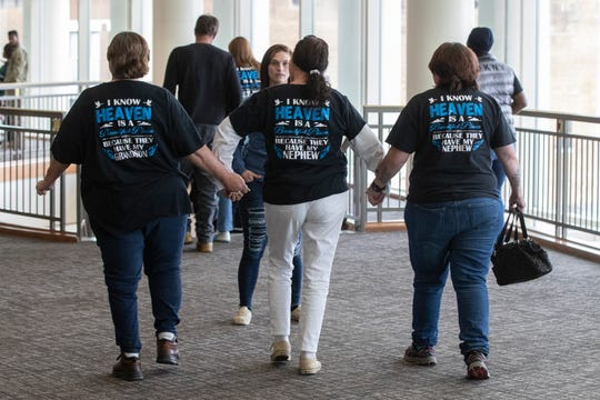 Family members wear custom shirts in remembrance of Hunter Payton, a 4-year-old who died from head injuries while in the foster care of Billy and husband Travis Embry-Martin in 2017. May 13, 2019