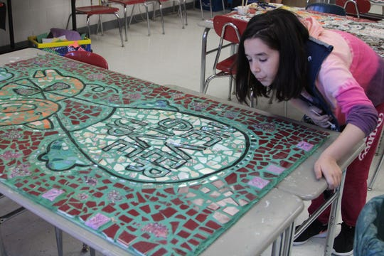 Brandi Budro, a fourth grade student at Garfield Elementary School, blows on one of eight large mosaics that her class helped work on Tuesday morning.