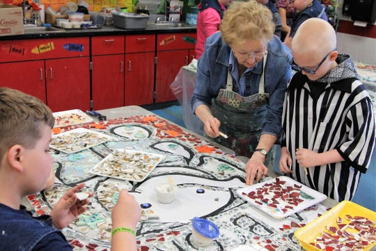 Delaware-based artist Virginia Corwin helps fourth grader Constantian French glue down small tiles on Tuesday.