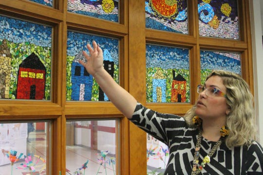 Chelsea Dipman, who teaches art at Garfield Elementary, stands next to several mosaics created by her students this school year under the tutelage of artist Gail Christofferson. Using a grant from the Ohio Arts Council, Dipman was able to bring in five artists between January and May to teach her students the art form.