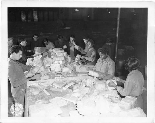 Soldiers in the Women's Army Corps 6888 Central Postal Directory Battalion sort mail in a warehouse in England. When the only all-female battalion to deploy overseas arrived in England it  faced a two-year backlog of mail that was handled in three months.