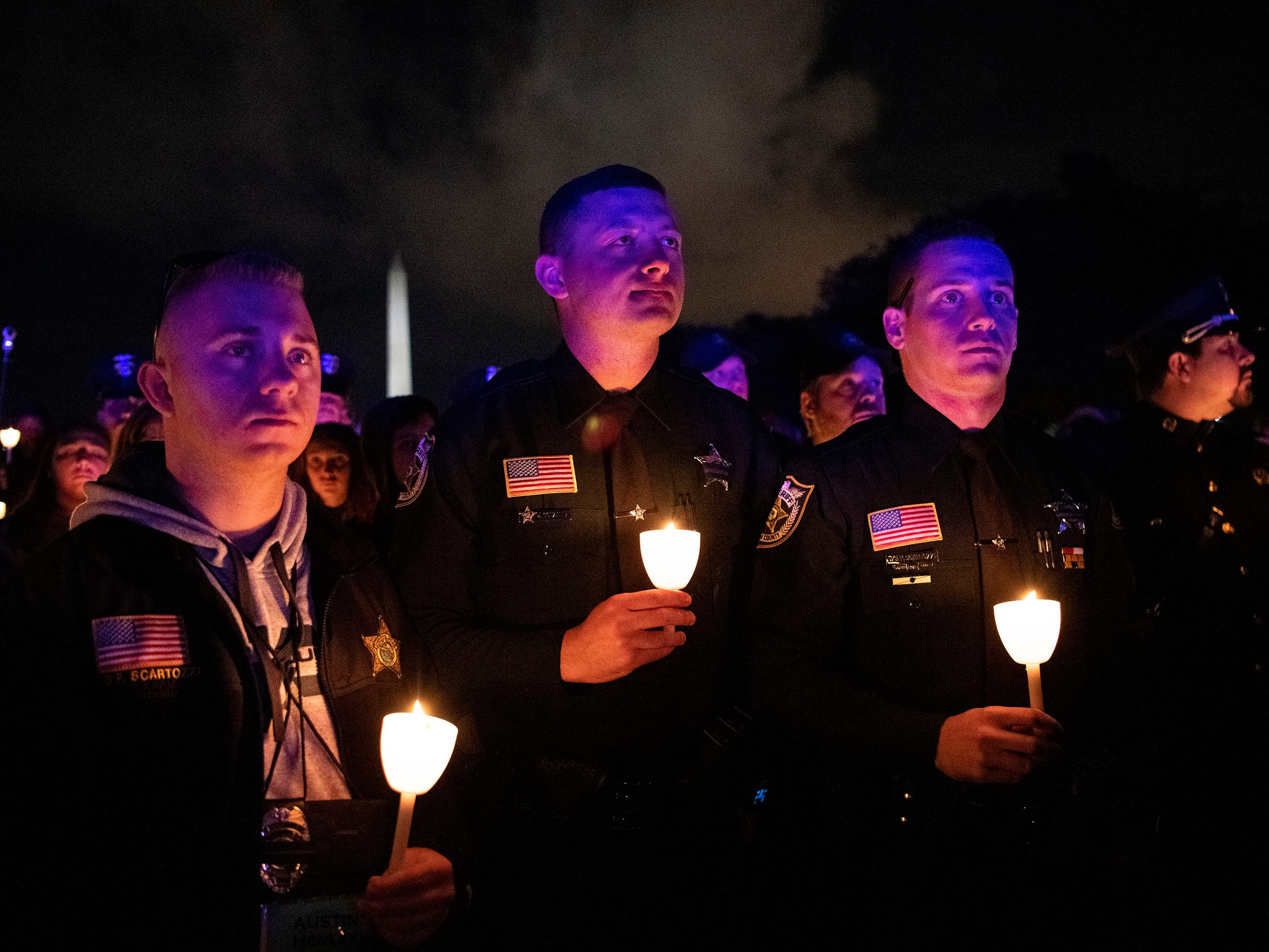 Austin Henley, left, Joshua Gonzalez and Patrick Scartozzi, all sheriff's deputies  in West Palm Beach, Florida, hold candles on the National Mall in Washington, DC during a candlelight vigil to honor slain law enforcement officers as part of Police Week in the nation's capital.
