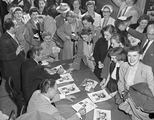 1954: Liberace (seated at left at table) and his brother George sign programs, autograph books, records, sheet music and other items in early morning hours after an evening concert at the Milwaukee Auditorium on May 3, 1954. Liberace signed autographs until 1:15 a.m. This photo was published in the May 4, 1954, Milwaukee Journal.