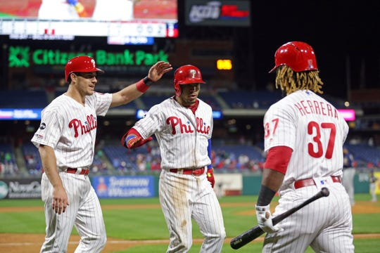 Cesar Hernandez of the Phillies is greeted at the dugout by J.T. Realmuto and Odubel Herrera after hitting a two-run home run in the fifth inning against the Brewers at Citizens Bank Park.