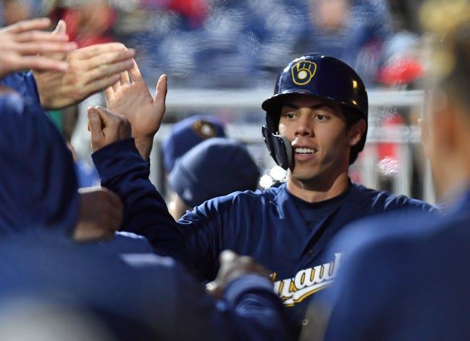 May 13, 2019; Philadelphia, PA, USA;  Milwaukee Brewers right fielder Christian Yelich (22) celebrates with teammates in the dugout after scoring a run during the first inning against the Philadelphia Phillies at Citizens Bank Park. Mandatory Credit: Eric Hartline-USA TODAY Sports