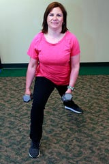 Cheryl Mashack shows the clock lunge exercise that is done in conjunction with the bicep curl exercise.