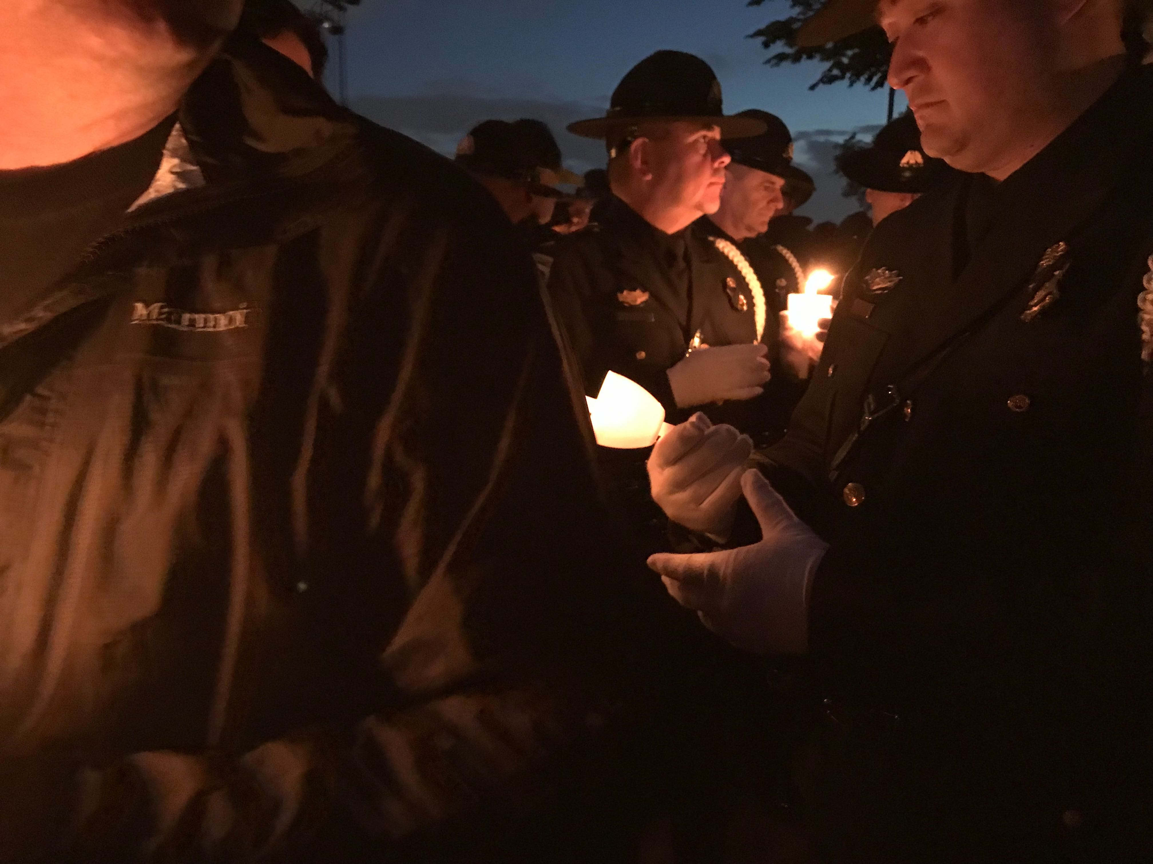 Law enforcement officers from various departments carry candles during the vigil.