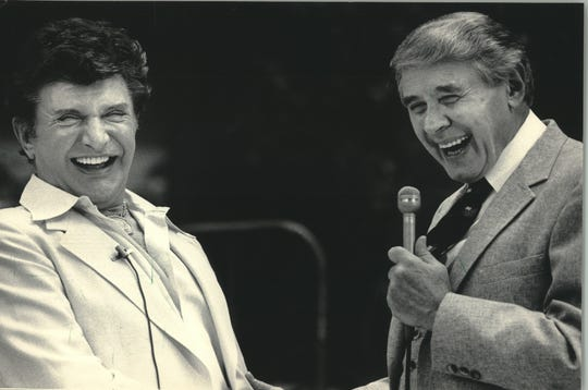 """1984: Liberace (left) receives the """"Piano Keys to the City"""" from Mayor Henry Maier at the Grand Avenue Mall on July 13, 1984. At the ceremony, the popular entertainer, born in West Allis, autographed a new piano for the Milwaukee School of the Arts. This photo was published in the July 14, 1984, Milwaukee Sentinel."""