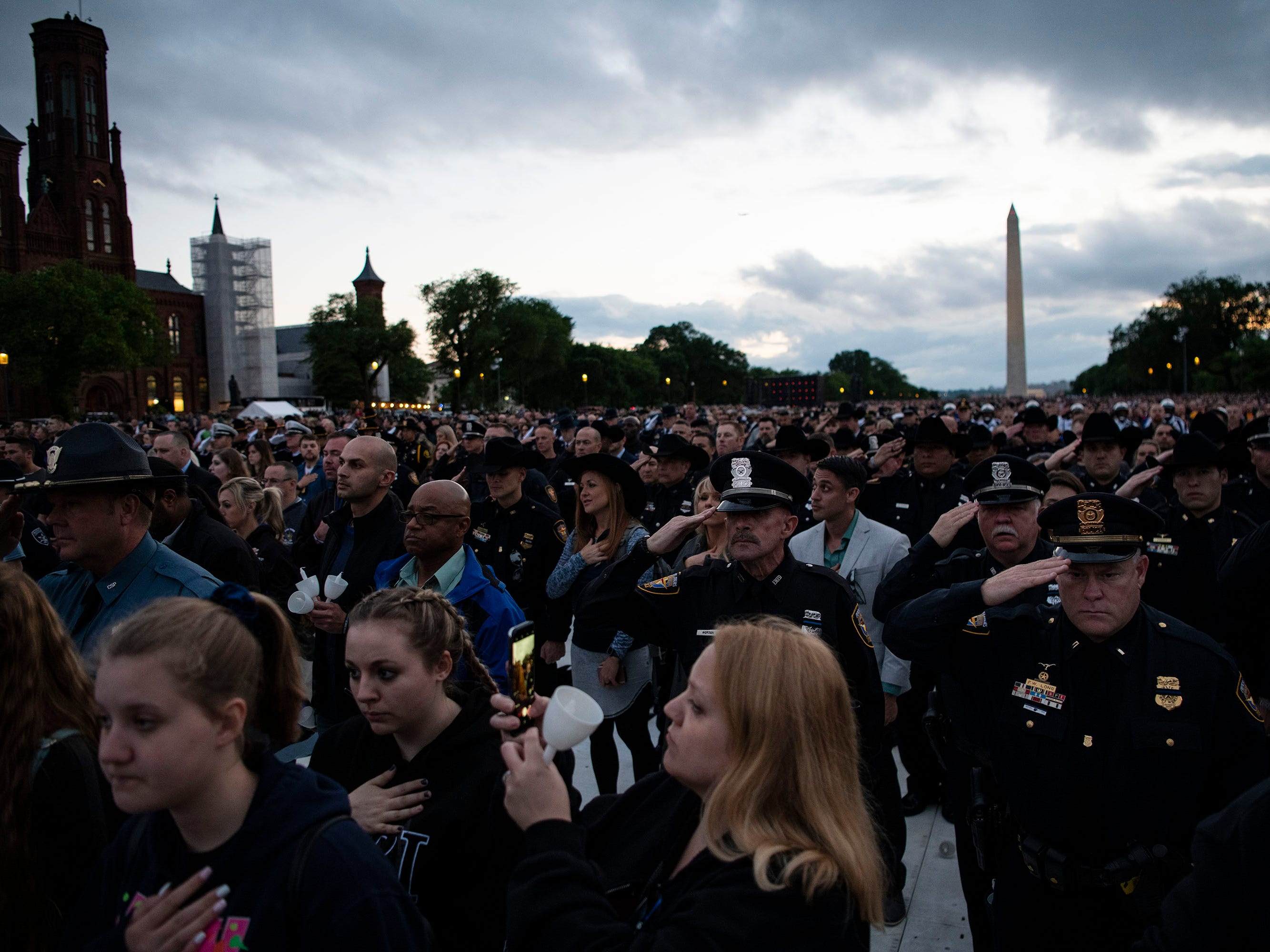 Law enforcement officers from all over the country salute alongside civilians while the National Anthem is sung at a candlelight vigil to honor slain police officers as part of Police Week in the nation's capital.