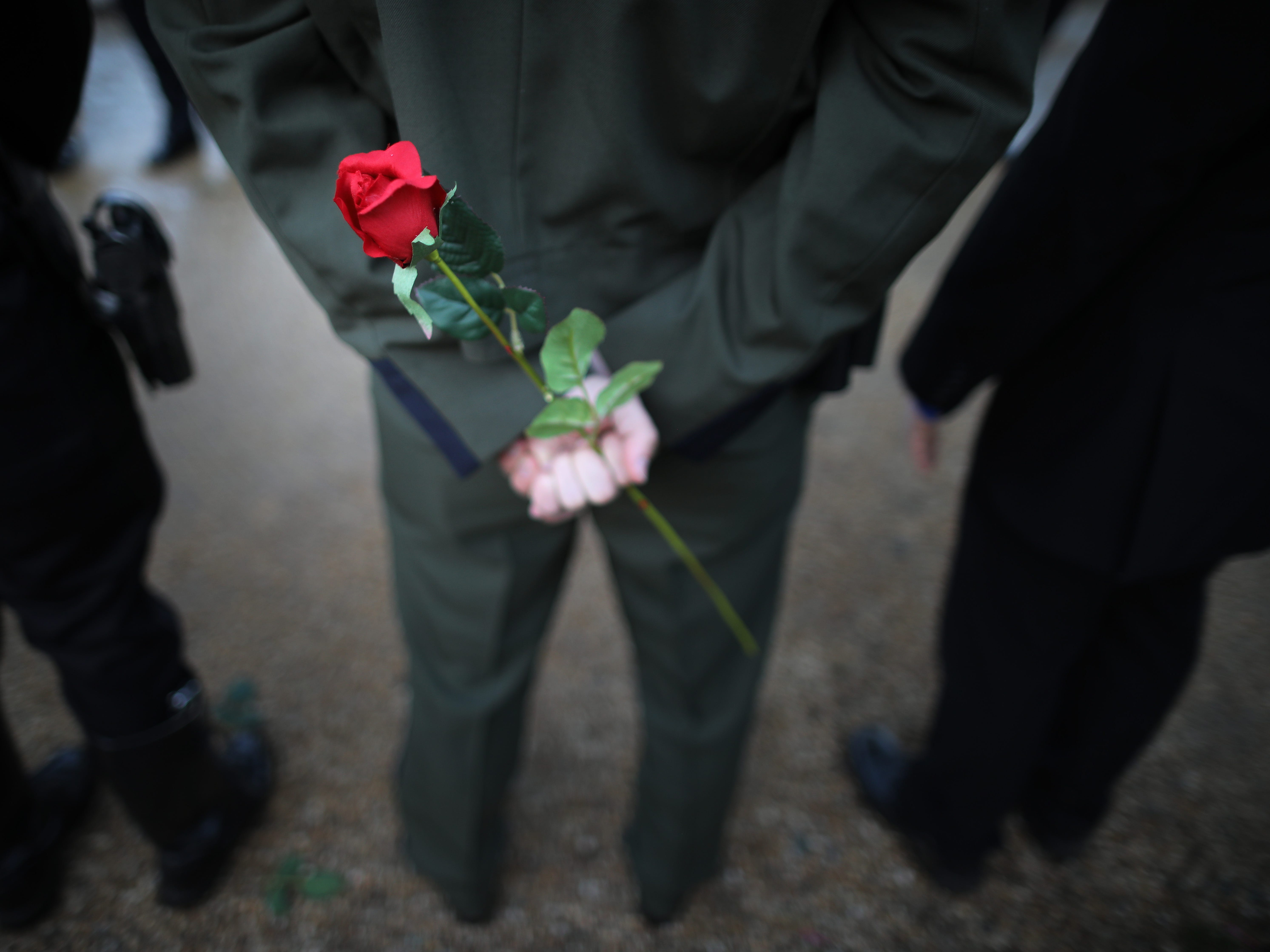 A law enforcement officer holds a rose to be given to family members of law enforcement officers who have died in the line of duty.