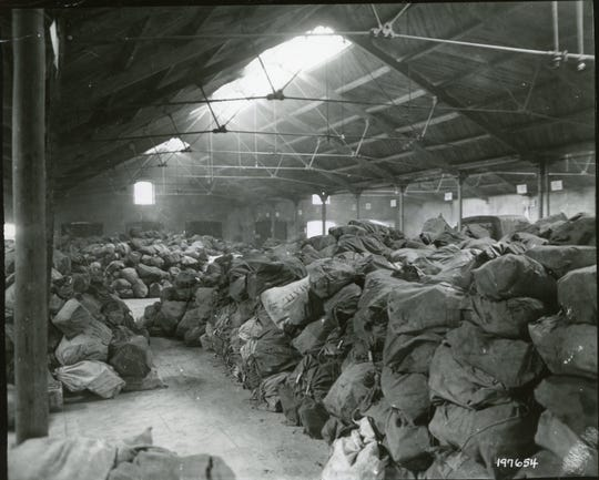 When the Women's Army Corps 6888 Central Postal Directory Battalion arrived in England it discovered a two-year backlog of mail including these bags stacked high in a warehouse.