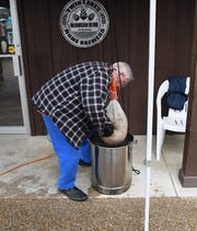 Twin Lakes Home Brewers club member Bob Bainbridge squeezes a large bag of grains to help it drain during Saturday's home brewing demonstration at Rapp's Barren Brewing Company in Mountain Home.