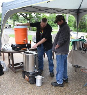 Twin Lakes Home Brewers members (from left) Joshua Sutherland and John Malcevicz talk about the whole-grain brewing setup the club had on display Saturday in Mountain Home.