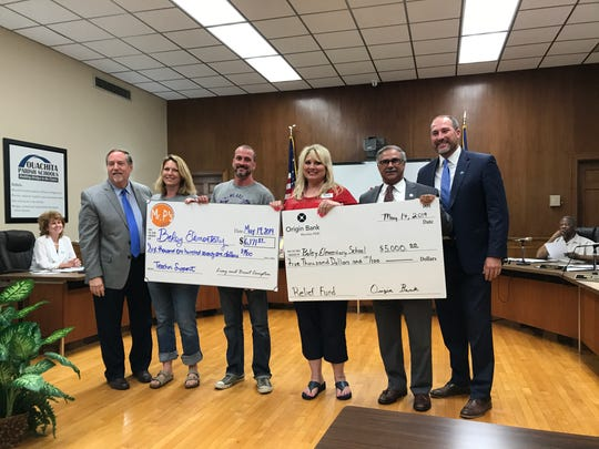 Representatives from Mr. P's Tees and Origin Bank presented checks for Boley Elementary to Superintendent Don Coker (far left) and Principal Sandy Bates (red shirt) at a Ouachita Parish School Board meeting on Tuesday.
