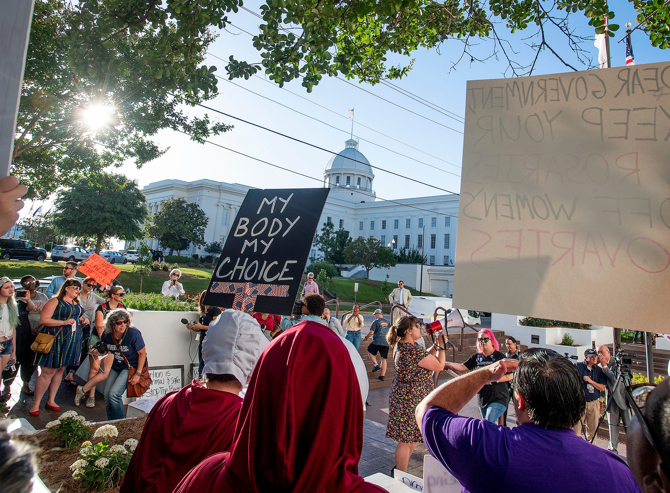 Lucia Hermo, with megaphone, leads chants during a rally against HB314, the near-total ban on abortion bill, outside of the Alabama Statehouse in Montgomery, Ala., on Tuesday May 14, 2019.