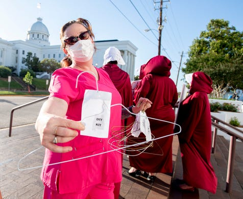 Laura Stiller hands out coat hangers as she talks about illegal abortions during a rally against HB314, the near-total ban on abortion bill, outside of the Alabama Statehouse in Montgomery, Ala., on Tuesday May 14, 2019.