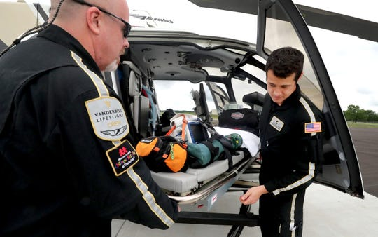 LifeFlight 5 base nurses Frank Edwards, left, and William Yasui show how the gurney on the new Airbus H130 is easy to load and unload. LifeFlight recently moved into a new facility at the Murfreesboro Airport.