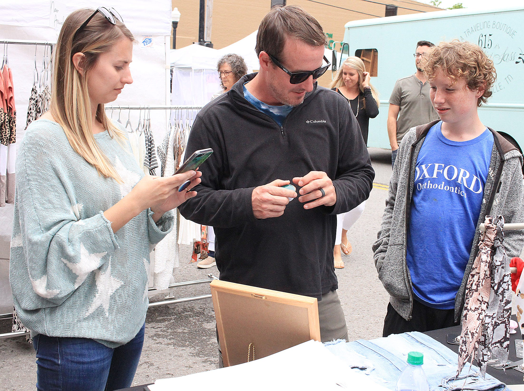 Katie Higgins shows some phone devices to Jared and Carson Kakalski at the Fashion Crawl in Gallatin , TN on Saturday, May 11, 2019.