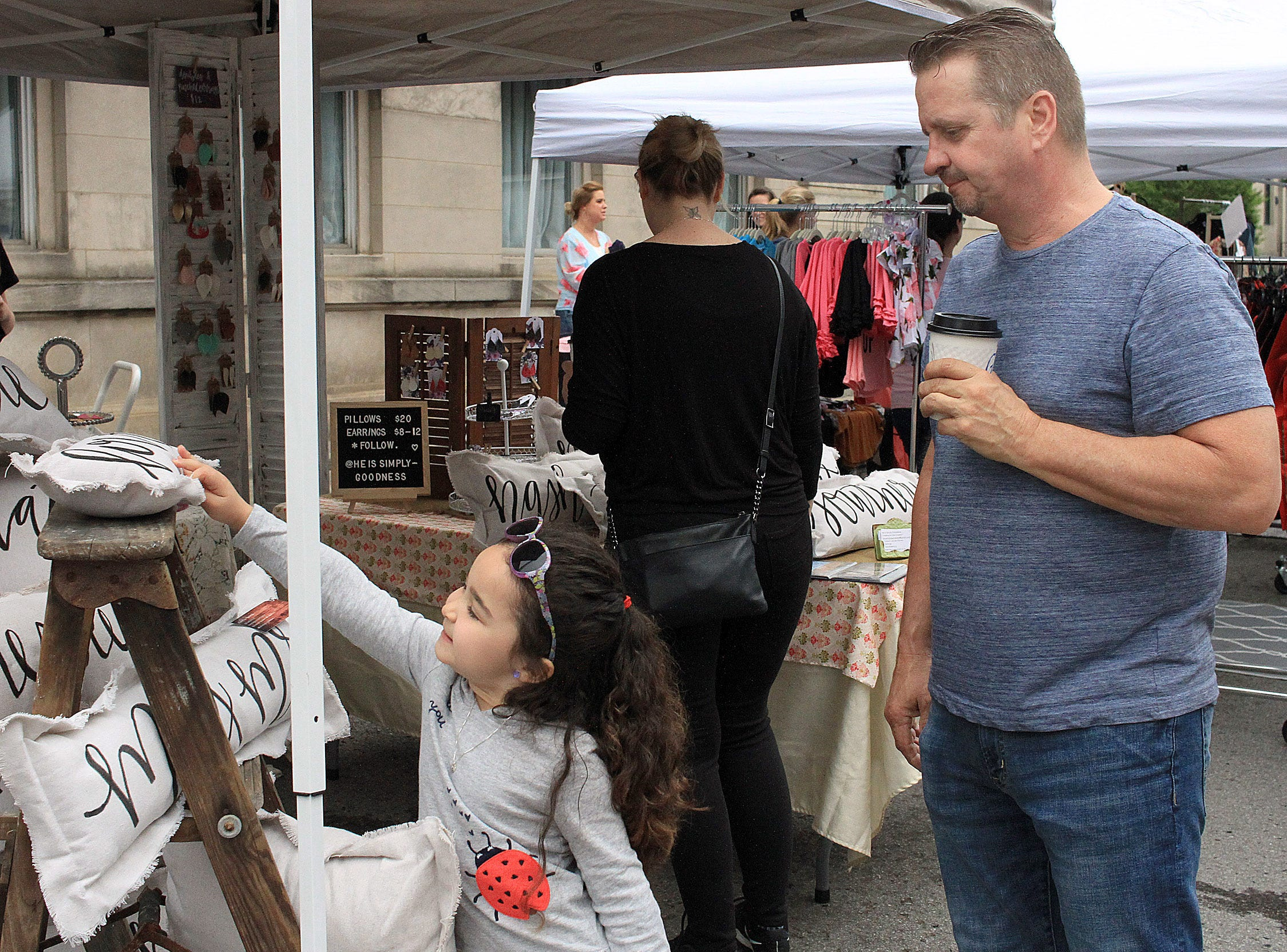 Ellie (5) with Dave Williams checks out some pillows at the Fashion Crawl in Gallatin, TN on Saturday, May 11, 2019.