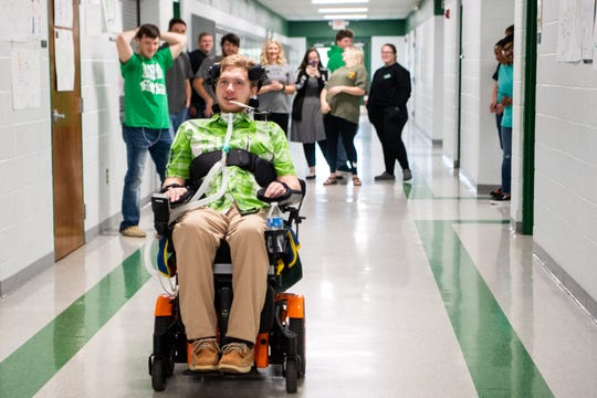 Jefferey Cox races down the hallway with his friends to determine the maximum MPH of his wheelchair at Houston County High School Thursday, April 18, 2019, in Erin, Tenn. Cox was paralyzed from the neck down during a football scrimmage last fall.