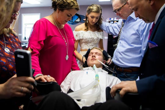 After a hard night and in pain, Jefferey Cox is prayed over by friends and family before going to prom with Landry Clardy on Saturday, April 20, 2019, in Erin, Tenn. The two have been dating since before the accident.
