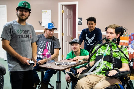 Jefferey Cox plays Madden NFL with Mayson Mills, Garrett Harvey, Michael Hughes and Victor Gomez, from left,  Thursday, April 18, 2019. Cox uses an adaptive controller which he operates with his straw, tongue and jaw.