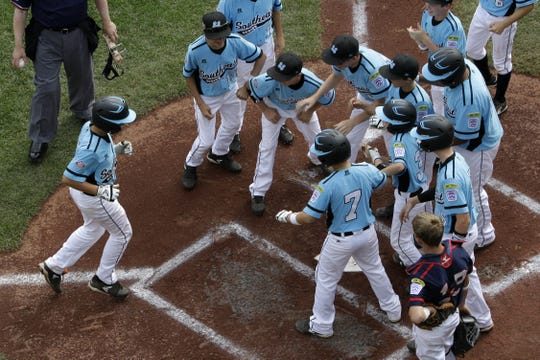 South Nashville's Zane Denton, left, trots home to greetings from his teammates after hitting a grand slam against Delaware on Aug. 19, 2013.