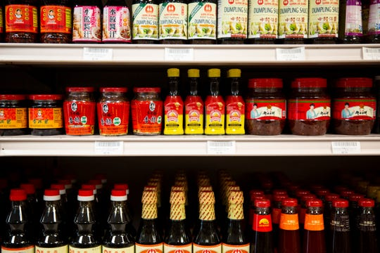 A variety of sauces line a shelf at Lee Asian Market in Naples on Monday, May 13, 2019. Many of the product labels and signs throughout the store include English descriptions so that they are more accessible to a wider audience in Naples.