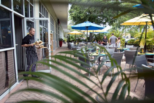 A chef brings out a couple of dishes at The Garden Cafe in Bonita Springs on April 2, 2016. The restaurant closed Saturday after operating more than three years.