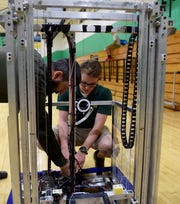 Newark Catholic teacher Russ Nelson and senior Ben Bemis set up the robotics team's robot, Atlas, for a presentation for elementary students from Blessed Sacrament and St. Francis. Nelson is robotics Instructor, STEM point person and Tech Coordinator at Newark Catholic.