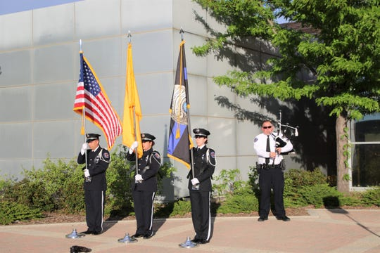 Members of the Farmington Police Department Honor Guard, Billy Canino, left, Sierra Tafoya, center, Cierra Manus, left, display colors as Jason Thornburg plays the bagpipes during the Annual San Juan County Law Enforcement Memorial and Candlelight Vigil on May 13 at the Farmington Museum at Gateway Park.