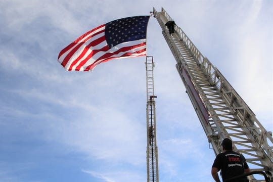 Farmington firefighters setup an American flag at the entrance of the Farmington Museum at Gateway Park for the Annual San Juan County Law Enforcement Memorial and Candlelight Vigil on May 13.